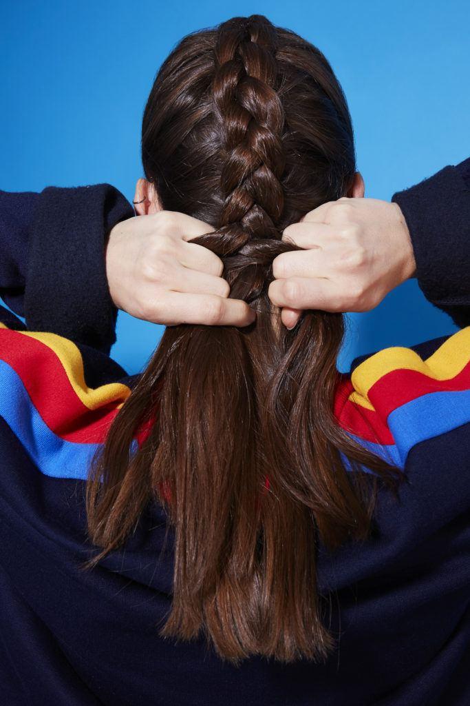 Comment faire une tresse hollandaise : Vue de dos d'une jeune fille brune tressant ses cheveux en une tresse hollandaise, portant un pull à rayures arc-en-ciel et se tenant debout sur un fond bleu