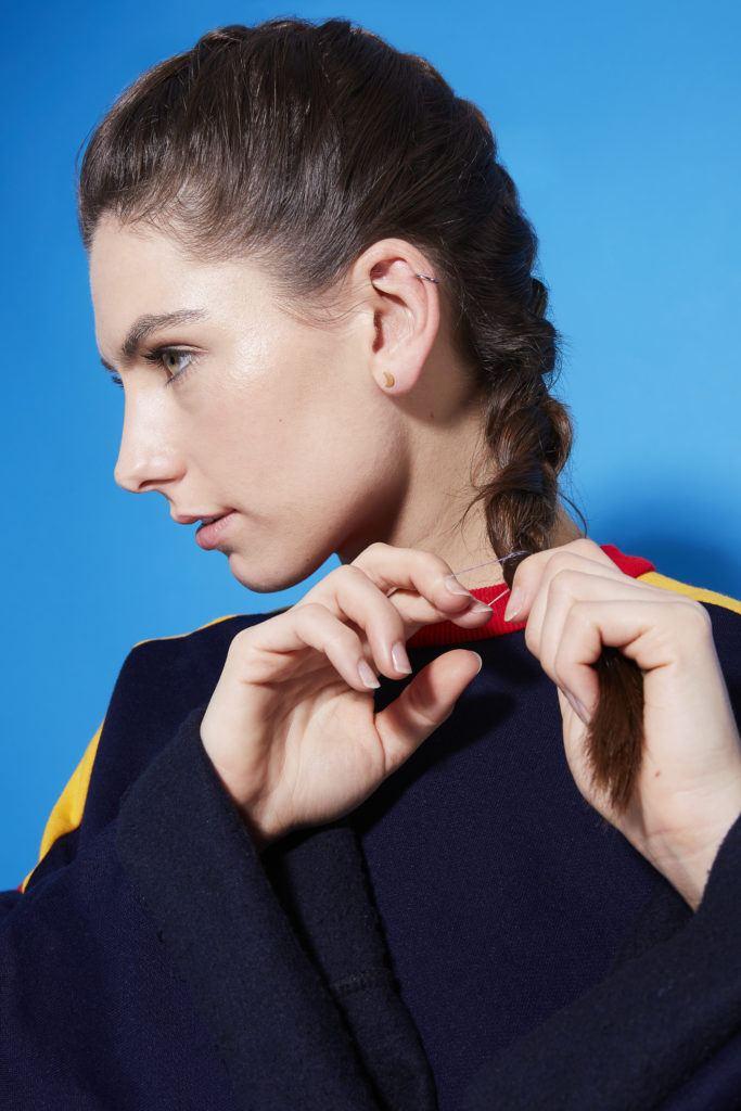 Comment faire une tresse hollandaise : Profil latéral d'une jeune fille brune nouant une tresse au bas de ses cheveux, debout sur un fond bleu