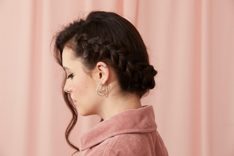 Femme aux cheveux brun chocolat, avec une tresse de couronne hollandaise sur le côté et une vrille de cheveux bouclés