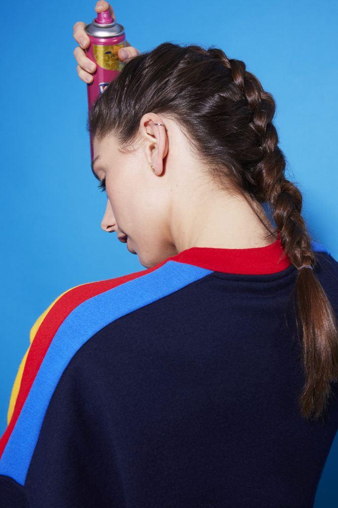 Comment faire une tresse hollandaise : Vue arrière d'une jeune fille brune avec une coiffure à tresses hollandaise qui se vaporise de la laque sur les cheveux