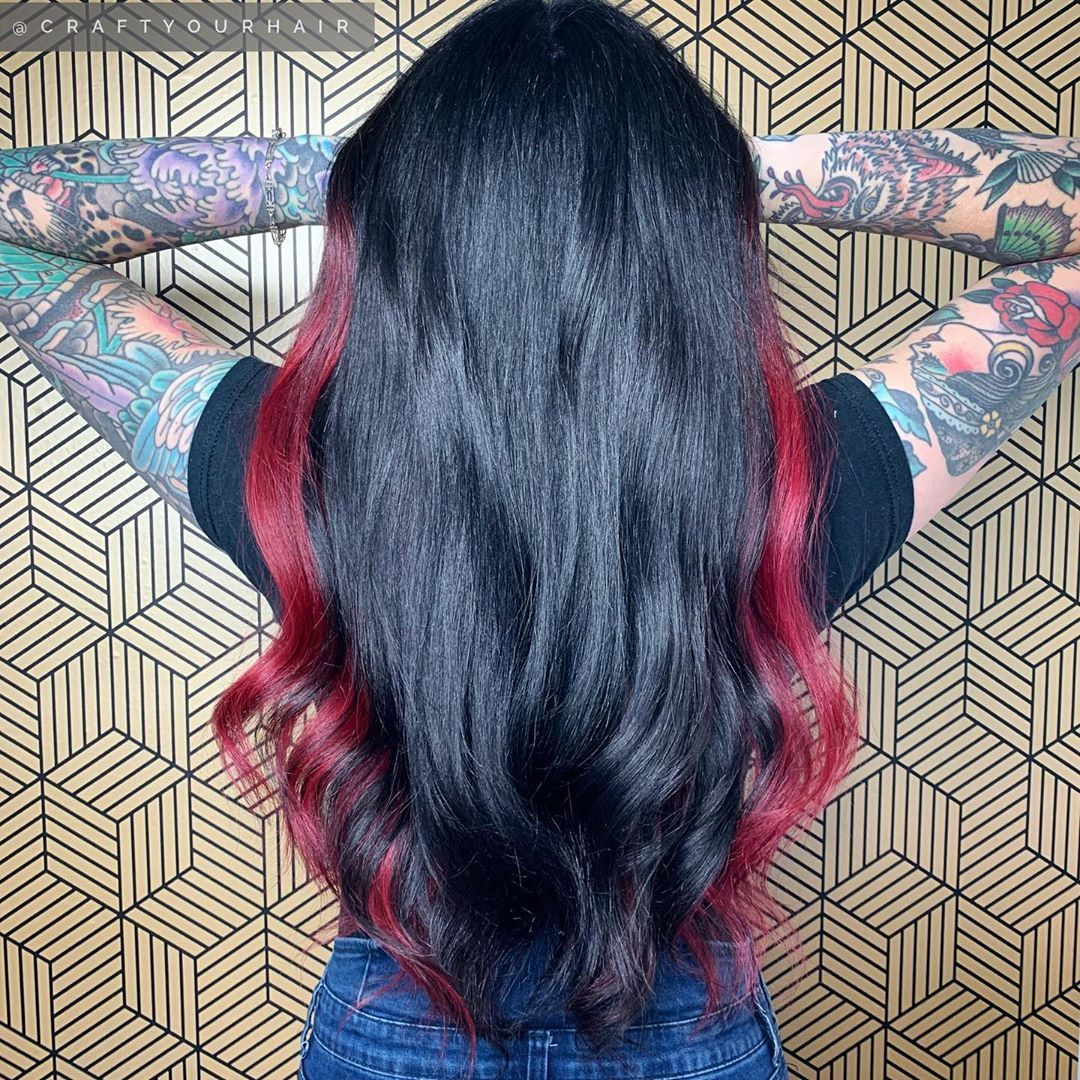 Femme aux longs cheveux noirs avec des reflets rouges sur les côtés
