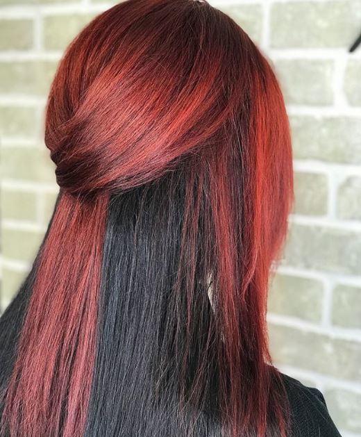 vue de dos d'une femme aux cheveux raides moitié rouges et moitié noirs