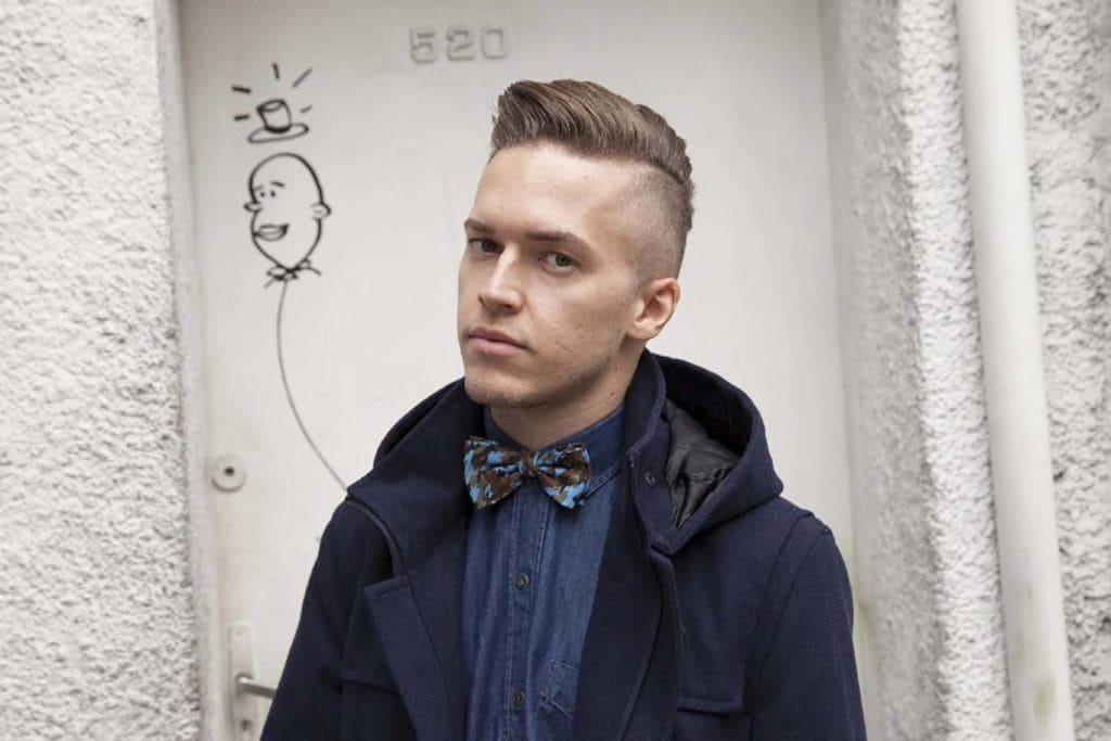Peigne conique sur une coupe de cheveux : Homme aux cheveux bruns, peignés et effilés, portant une chemise en denim, un manteau bleu marine et un nœud papillon