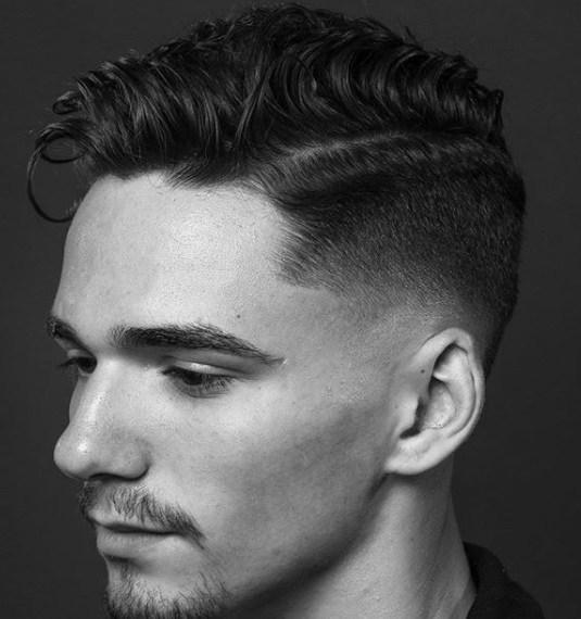 Peigne conique sur une coupe de cheveux : Photo en noir et blanc d'un homme avec une coupe de cheveux bouclée et effilée