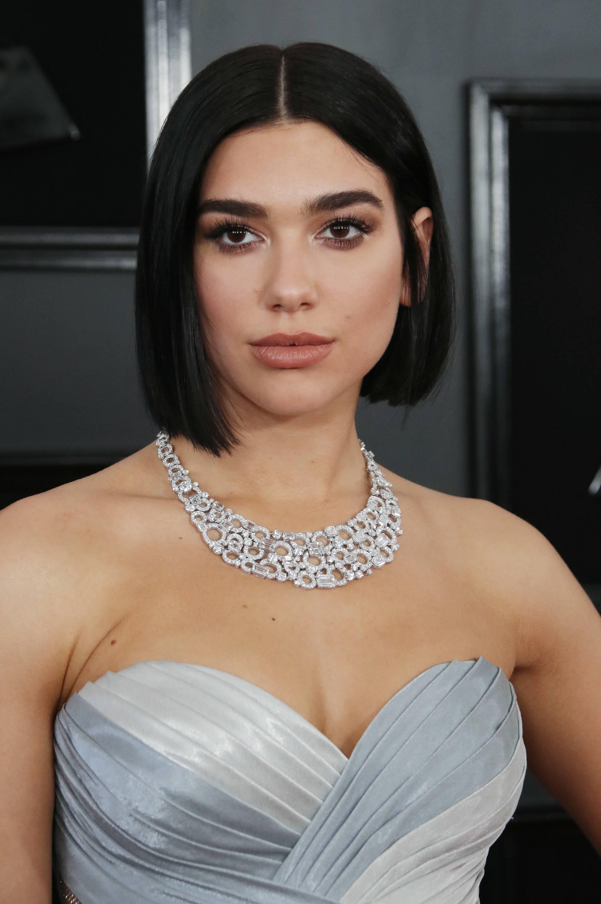 Dua Lipa avec une coupe de cheveux au carré, portant un collier et une robe argentée décolletée