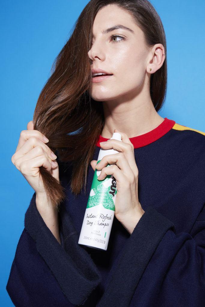 Comment faire une tresse hollandaise : Photo d'une jeune fille brune appliquant du shampoing sec sur ses cheveux, sur fond bleu