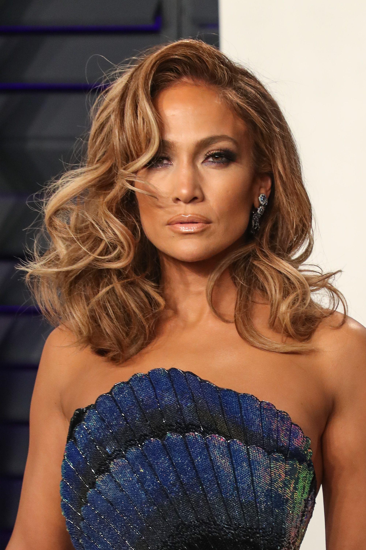 Les points forts et les points faibles : Jennifer Lopez avec des cheveux bouclés de longueur moyenne et une frange latérale.
