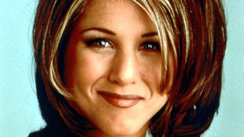 Coupe de cheveux de Rachel : Jennifer Aniston avec une coupe de volume à la longueur des épaules avec de longues épaisseurs et une coiffure des années 90 à frange latérale.