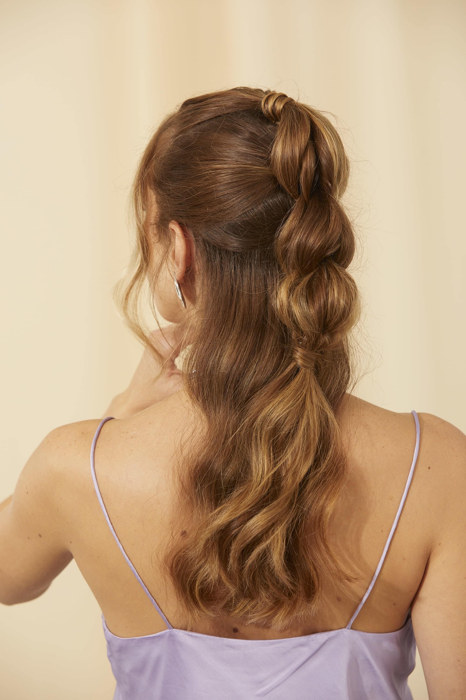 Femme brune avec une coiffure en queue de cheval à demi-bulle