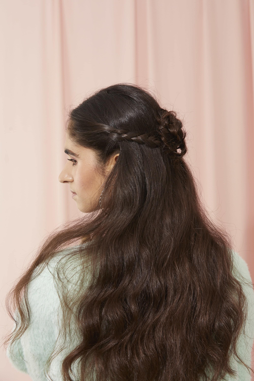 Femme aux cheveux bruns très longs et ondulés, coiffée en chignon tressé en forme de fleur à mi-hauteur