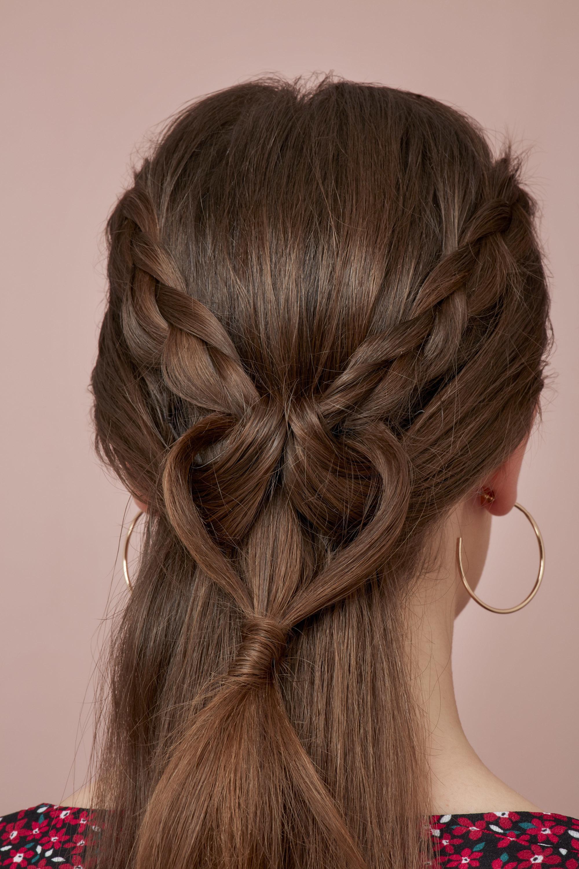 Les cheveux de la Saint-Valentin : Gros plan sur le dos d'une brune avec une coiffure tressée en forme de coeur d'amour