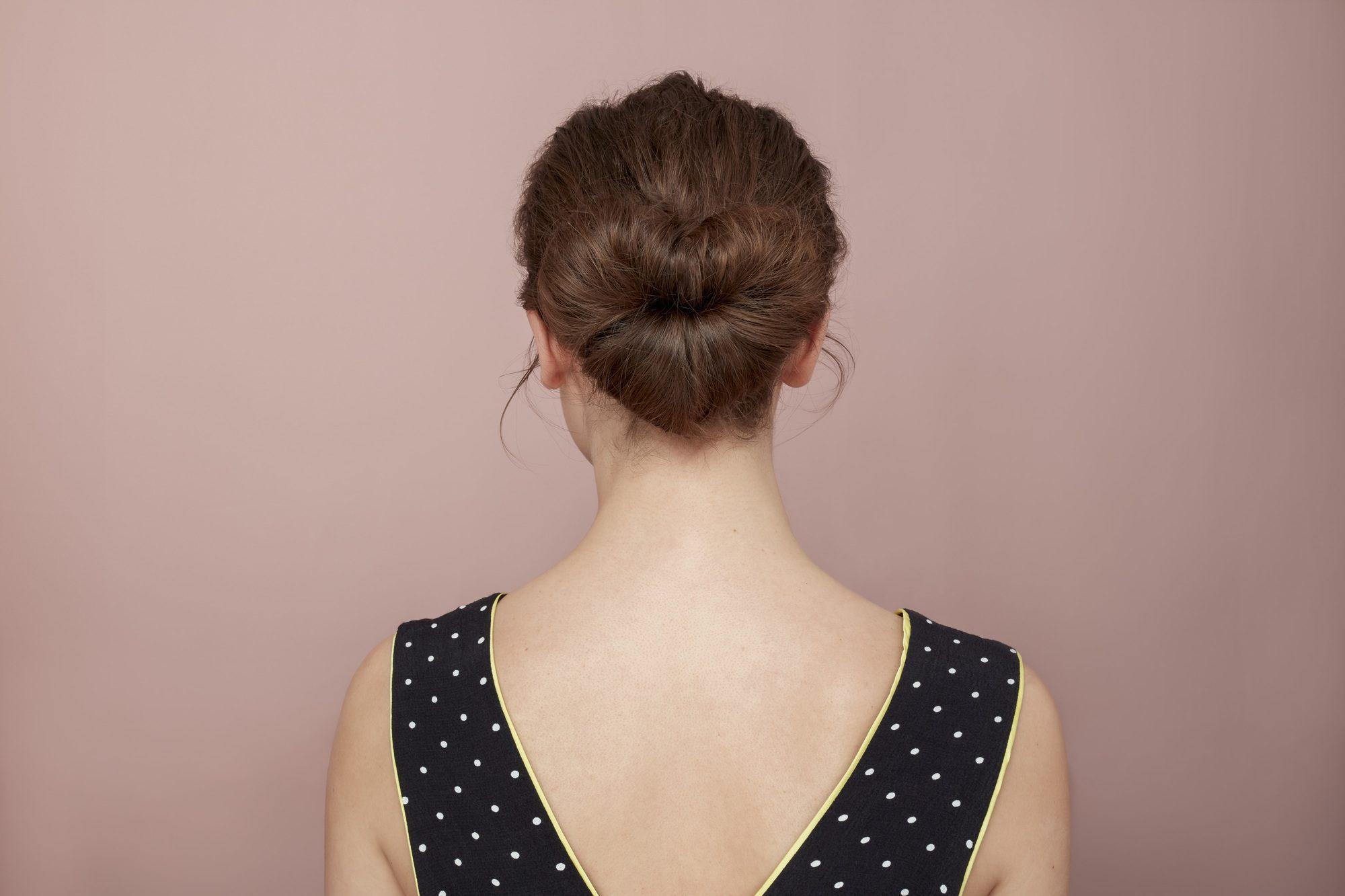 Les cheveux de la Saint-Valentin : Vue arrière d'un mannequin brun avec ses cheveux en chignon en forme de coeur, portant une robe noire et blanche à pois en V