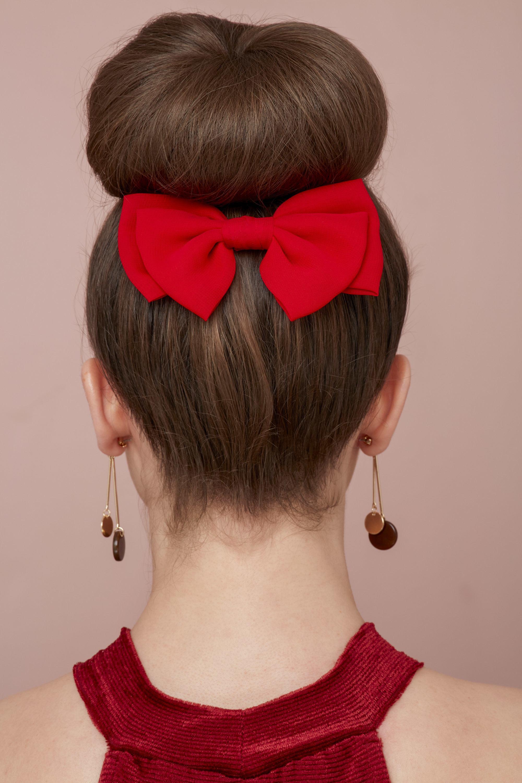 Les cheveux de la Saint-Valentin : Vue de derrière d'une femme brune avec ses cheveux dans un chignon de ballerine haut avec un accessoire en forme de nœud rouge, portant une robe rouge