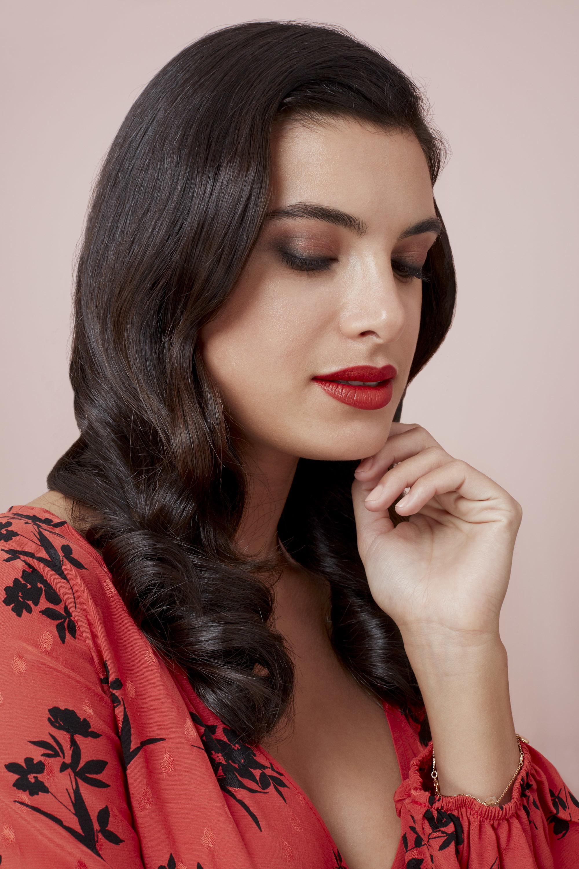 Les cheveux de la Saint-Valentin : Femme brune avec des vagues hollywoodiennes polies, portant une robe rouge à fleurs et du rouge à lèvres