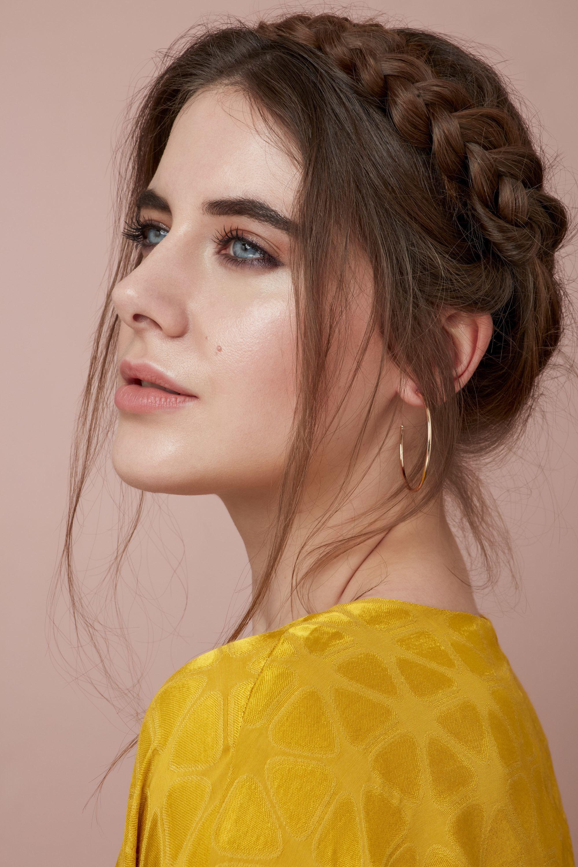 Les cheveux de la Saint-Valentin : Gros plan d'une femme brune avec ses cheveux en tresse de laitière avec des mèches défaites, portant un haut jaune