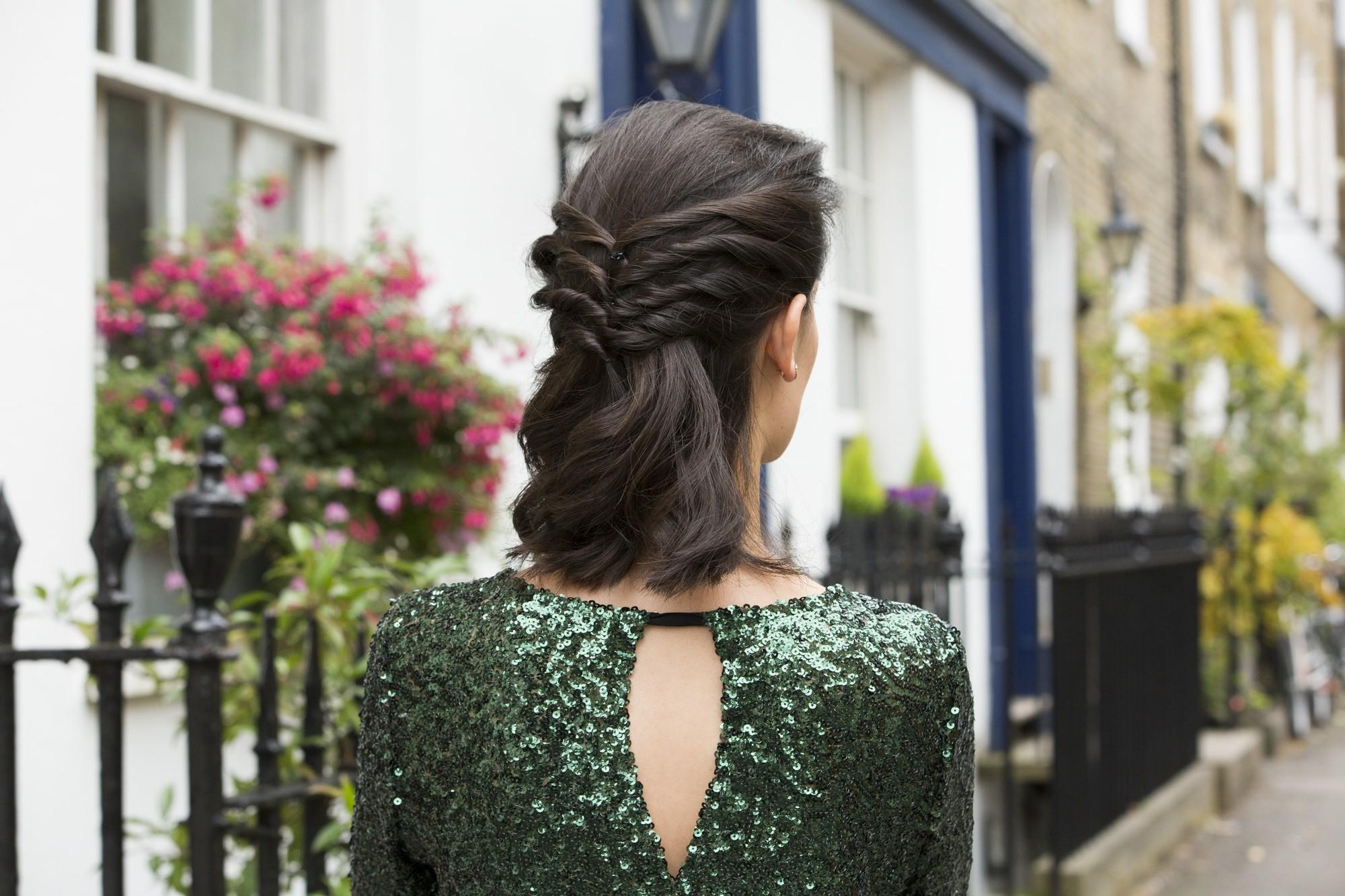 gros plan d'une femme à la coiffure tordue, mi-haute, mi-basse, portant une robe scintillante et posant à l'extérieur
