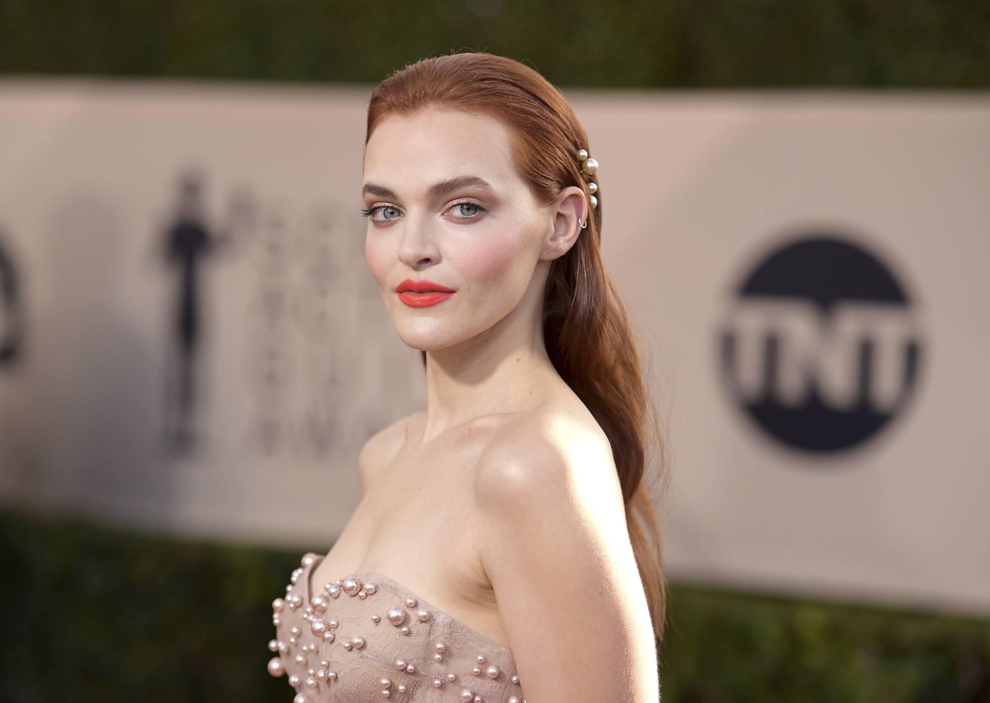 gros plan de Madeline brasseuse aux cheveux lisses et perlés, portant une robe nacrée