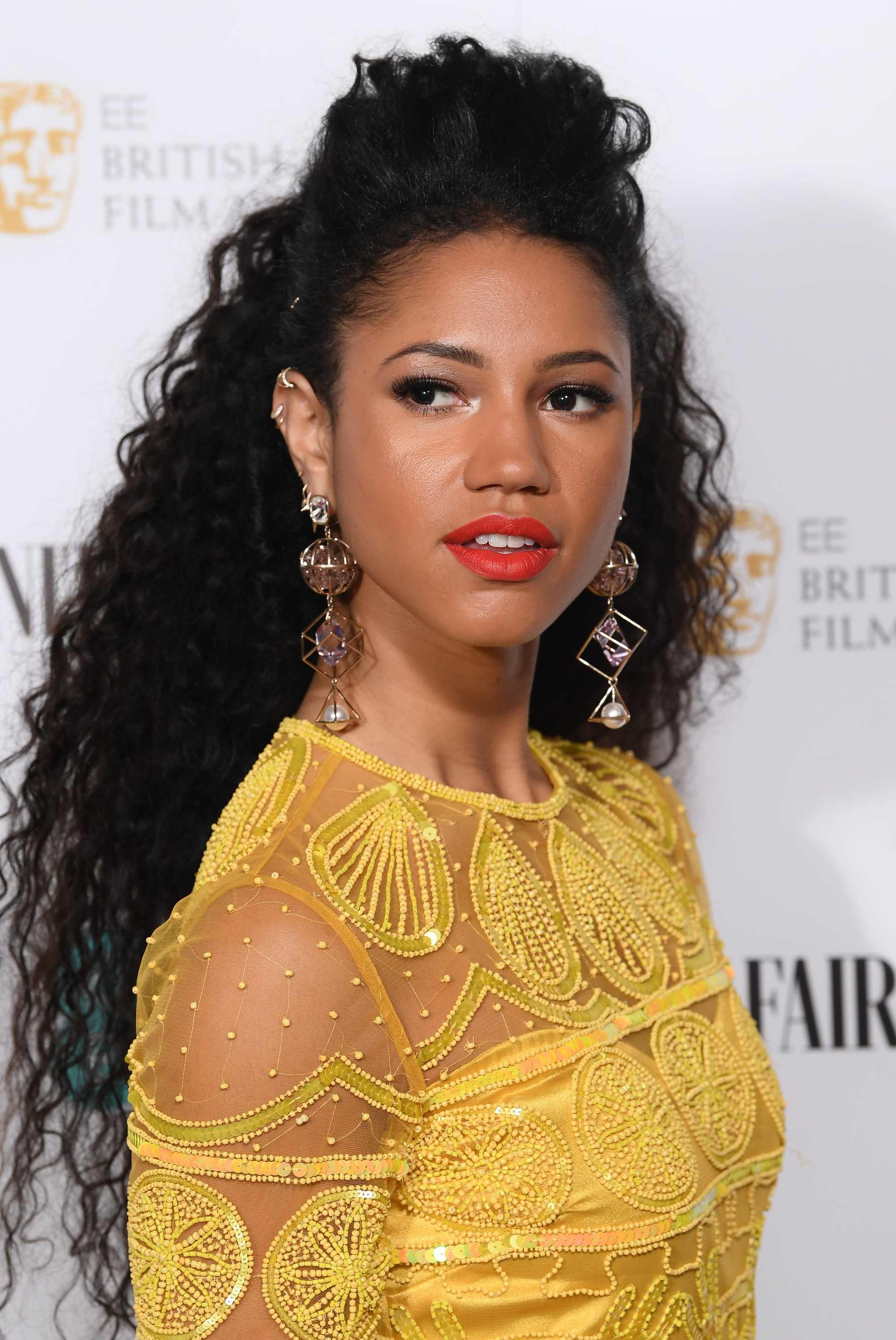 Célébrités de la Saint-Valentin : plan de côté de Vick Hope avec de longues boucles marron foncé, coiffée en chignon mi-hauteur, mi-en bas, portant une robe en dentelle jaune avec des boucles d'oreilles chic sur le tapis rouge