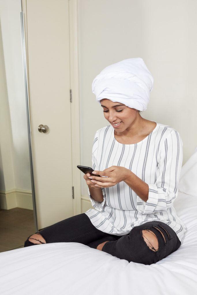 femme aux longs cheveux bouclés brun foncé dans une chambre à coucher, attachée à un t-shirt