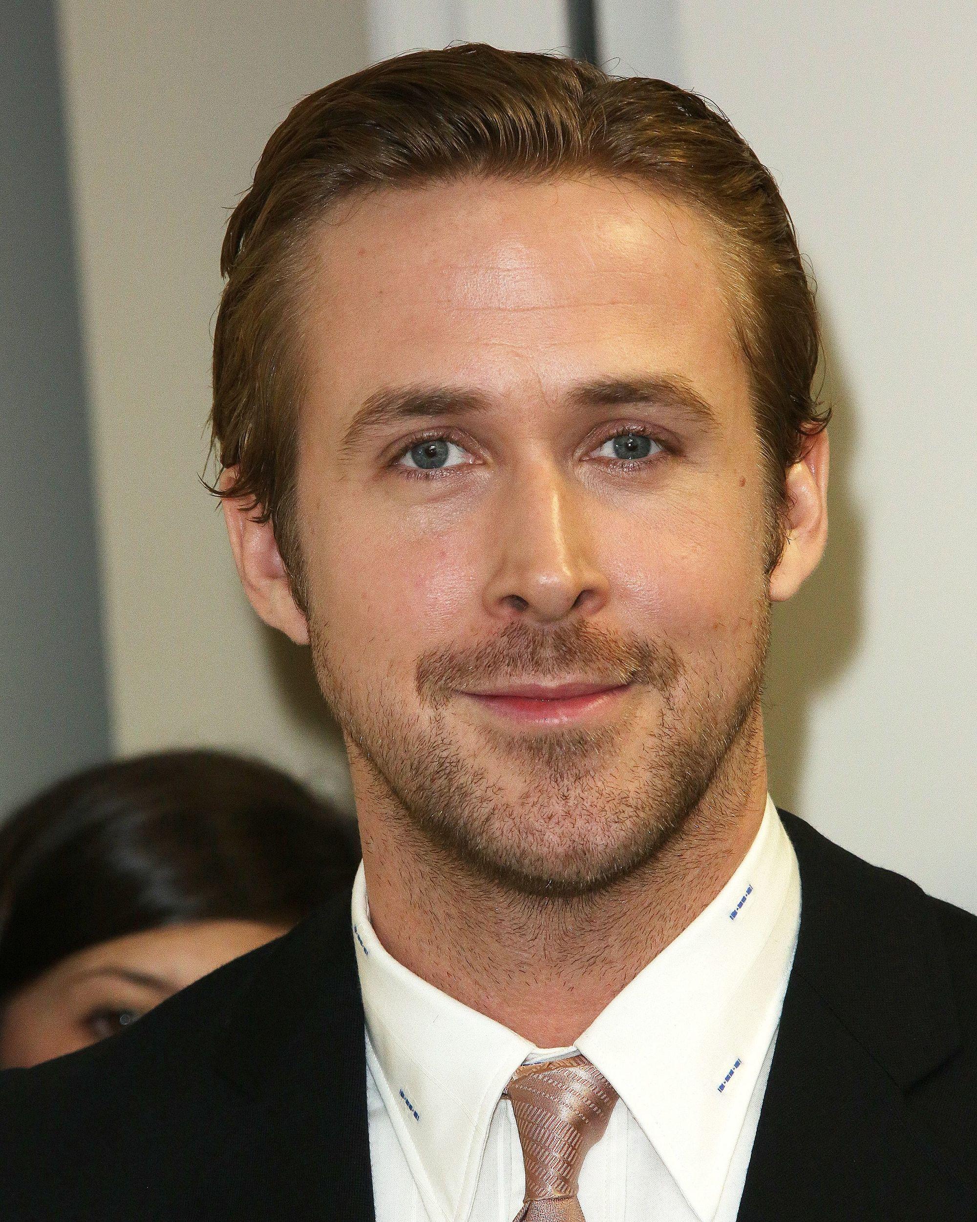 Coupe de cheveux de Ryan Gosling : Ryan Gosling avec une élégante coiffure brossée sur le dos, avec des cheveux courts et portant un costume et une cravate