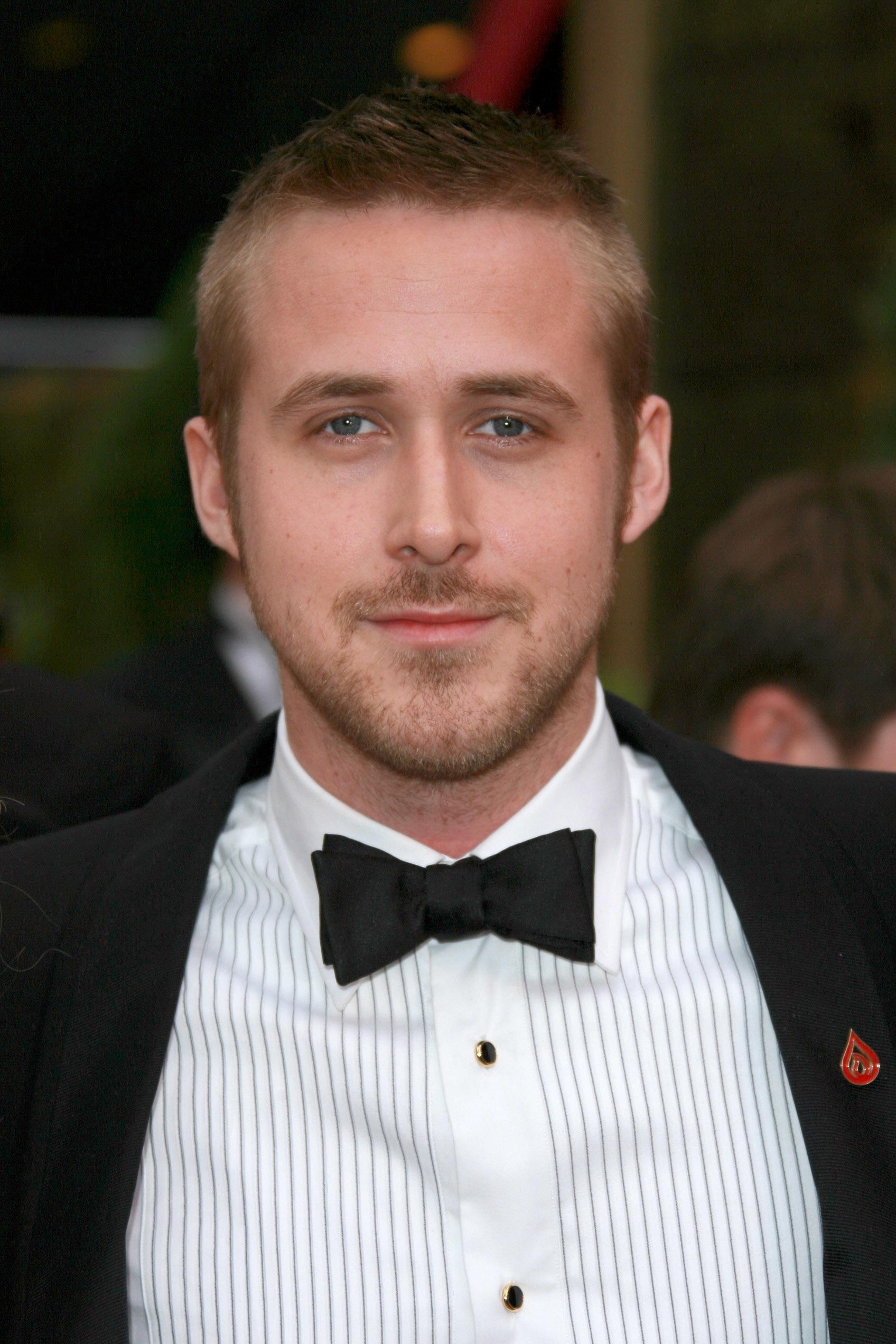 Coupe de cheveux de Ryan Gosling : Ryan Gosling avec un peigne mi-long avec des côtés courts et effilés, portant une chemise bleue