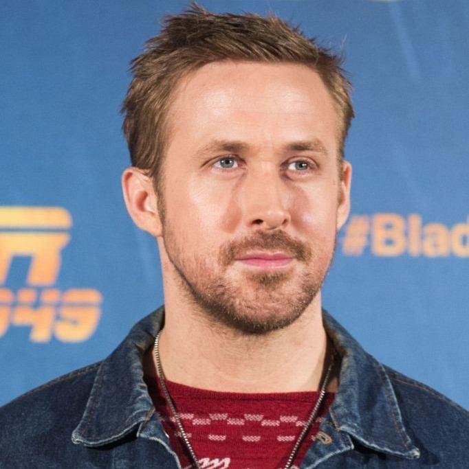 Coupe de cheveux de Ryan Gosling : Ryan Gosling avec une coupe de cheveux à pointes, portant un haut à motifs rouges et une veste en jean