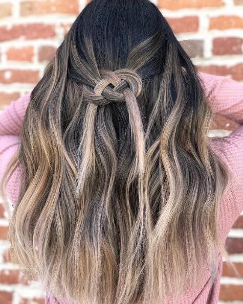 Femme aux cheveux bruns de balayage dans une tresse de nœud celtique