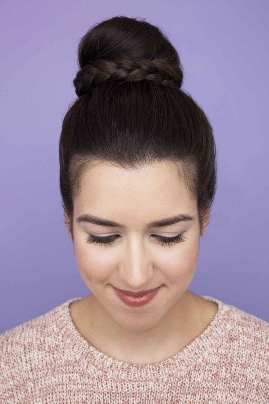 Femme aux cheveux bruns foncés dans un chignon tressé