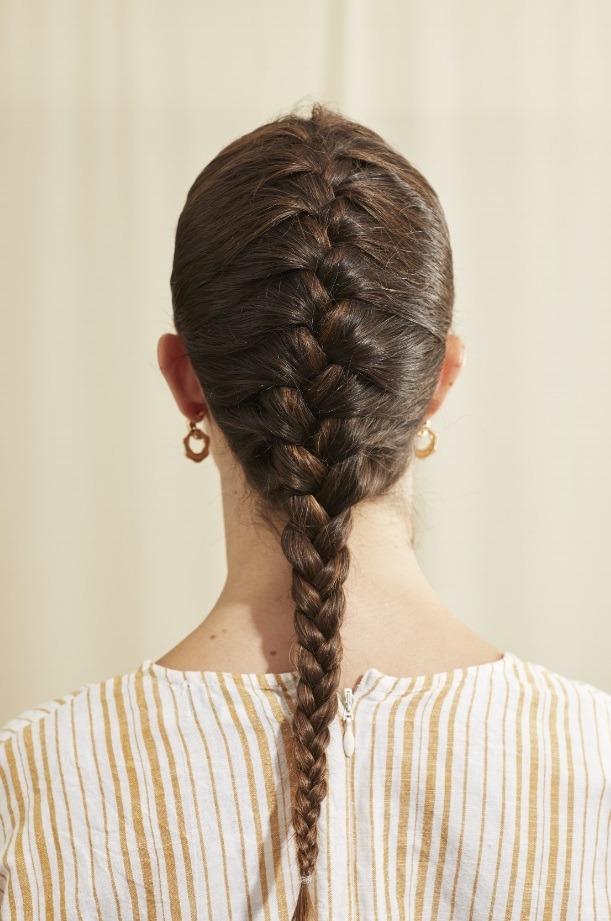 Femme aux longs cheveux bruns avec une tresse française