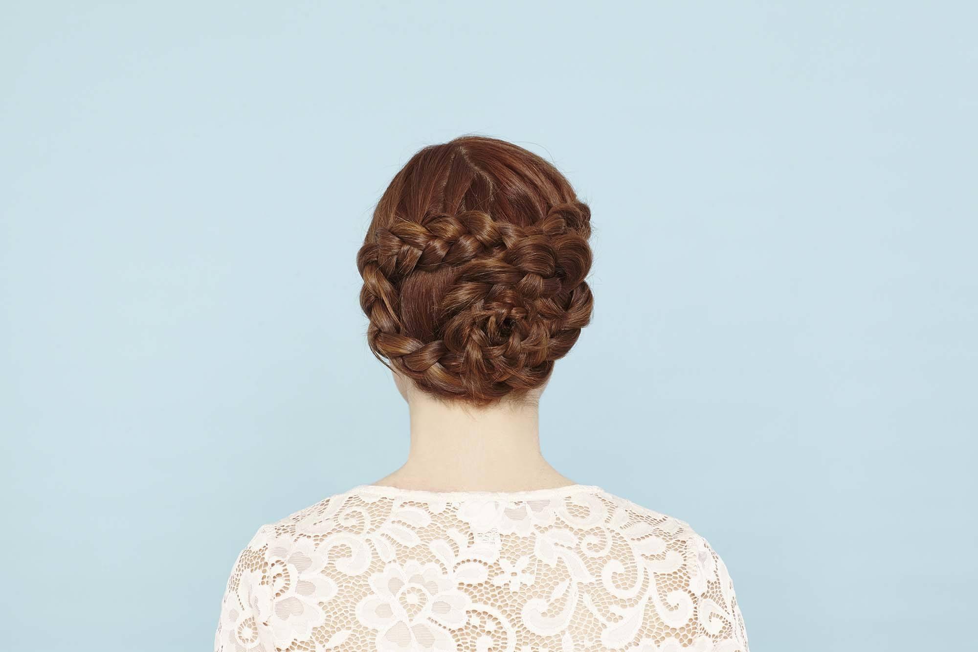 Femme aux cheveux roux dans un updo de tresses de fleurs