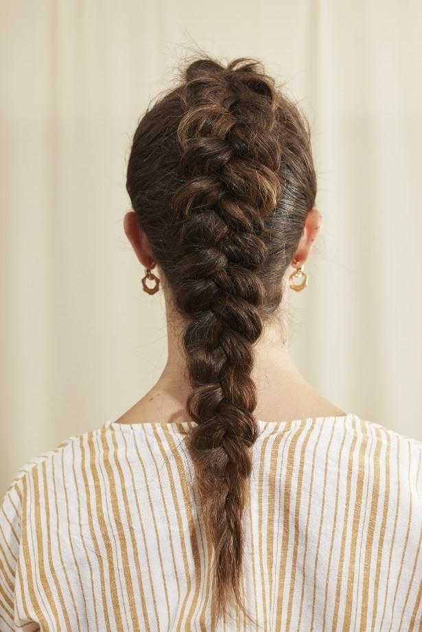 Femme aux longs cheveux bruns avec une tresse hollandaise
