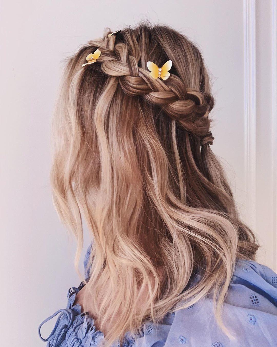 Femme aux cheveux blonds beiges dans une tresse en demi-lune avec des pinces papillon