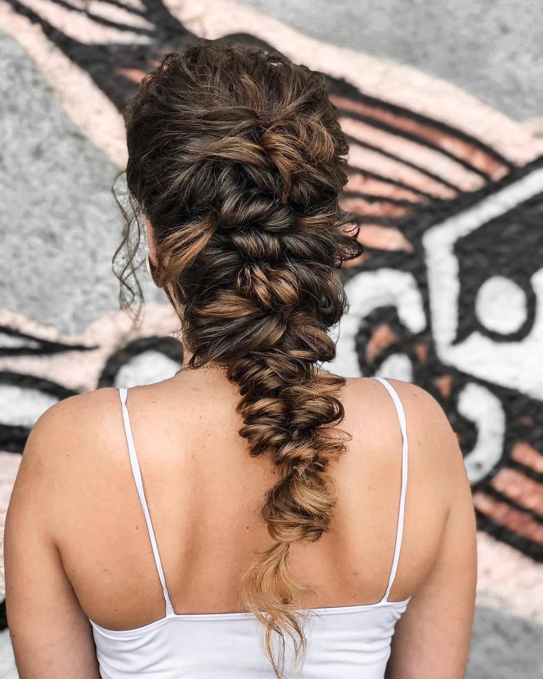 Femme brune avec une longue coiffure grecque en tresse