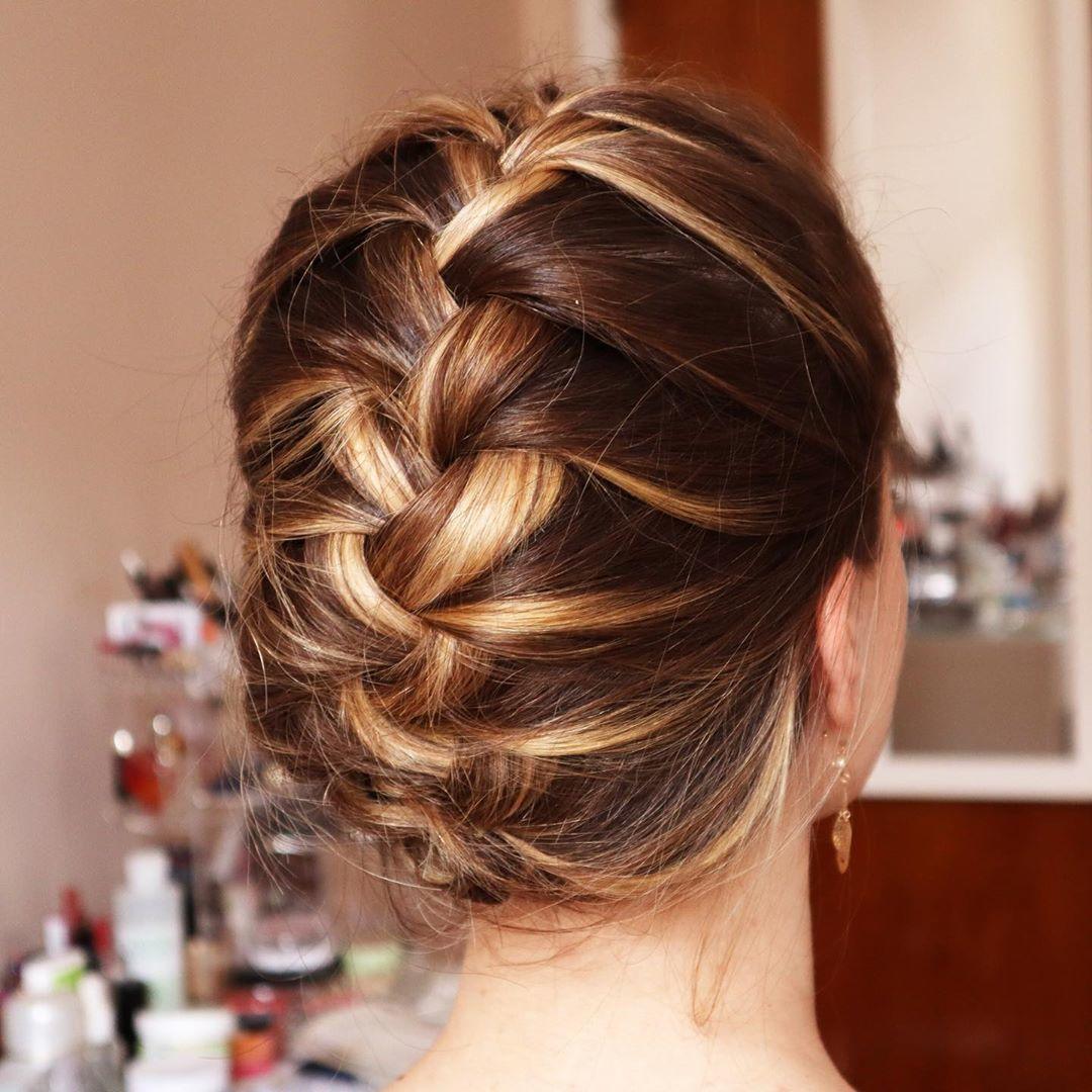 Femme aux cheveux bruns soulignés dans un updo français tressé