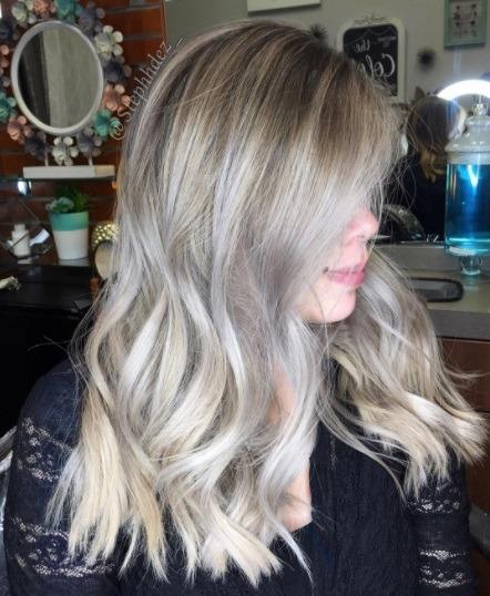 photo de profil d'une femme aux cheveux blonds lilas bouclés de longueur moyenne