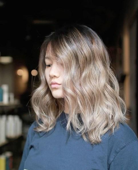 Blond cendré ombre : Photo d'une femme aux cheveux ondulés de couleur brun cendré ombre, à la longueur des épaules