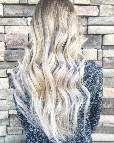 Blond cendré ombre : Vue de dos d'une femme aux longs cheveux ondulés blond cendré platine, portant du gris