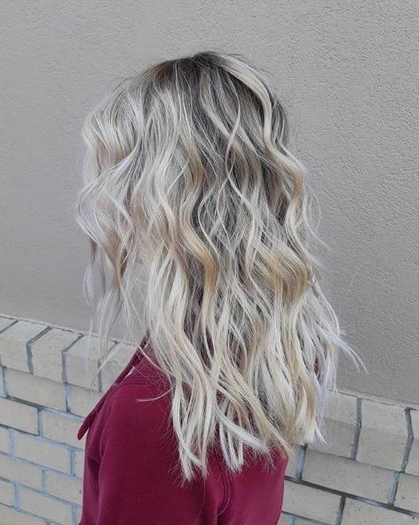 Blond cendré ombre : profil d'une femme aux cheveux blond cendré champagne, coiffée en boucles libres, portant un haut de couleur baie