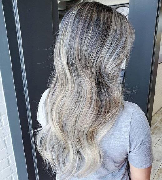 Ombre blonde cendrée : Vue de dos d'une femme aux cheveux ondulés d'un blond cendré gris fumé, portant un t-shirt gris