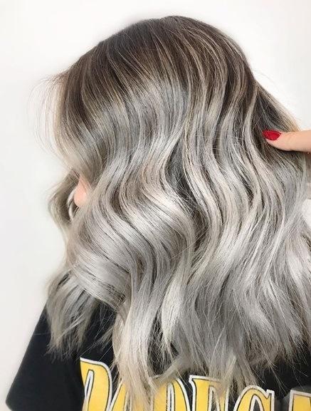 Blond cendré ombre : Gros plan d'une femme aux cheveux gris cendré ondulé argenté à l'épaule