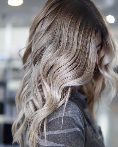 Blond cendré ombre : Gros plan d'une femme aux cheveux ondulés d'un blond cendré avec des racines d'ombre grises