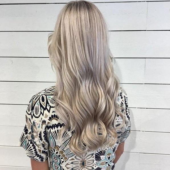 Ombre blonde cendrée : Vue de dos d'une femme aux longues vagues blondes crémeuses, portant un haut à motifs