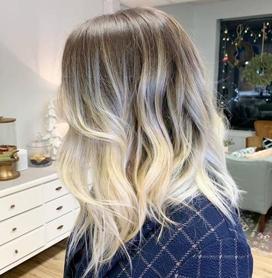 Blond cendré ombre : Vue de côté d'une femme aux cheveux bruns à blonds sombres de longueur moyenne, coiffée en vagues douces, portant une chemise à carreaux