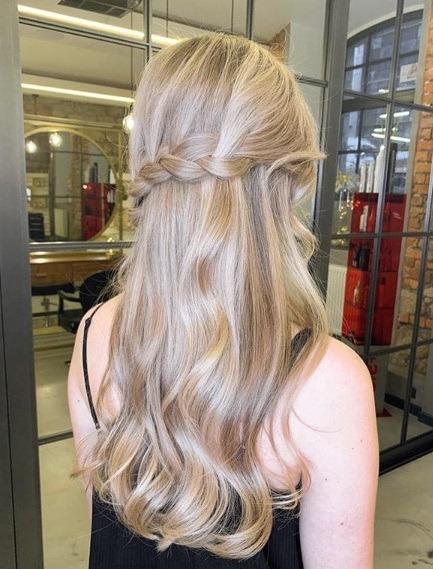 Blond cendré ombre : Vue de dos d'une femme aux longs cheveux blonds beige ondulés, coiffée en demi-hauteur torsadée