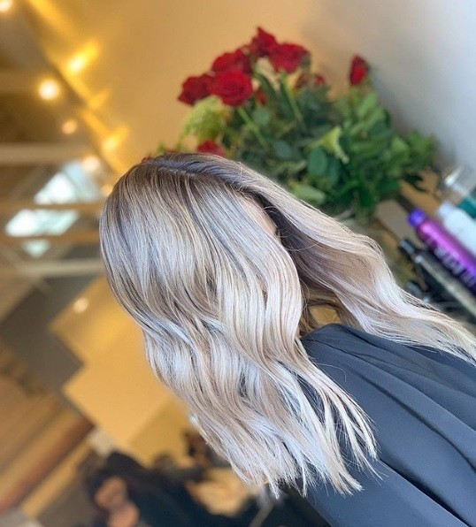 Ash blonde ombre: Photo of a woman with shoulder length, wavy light ash blonde ombre hair in a salon