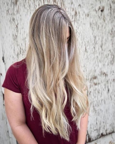 Blond cendré ombre : Photo d'une femme aux longs cheveux ondulés d'un blond vanille, portant un t-shirt marron