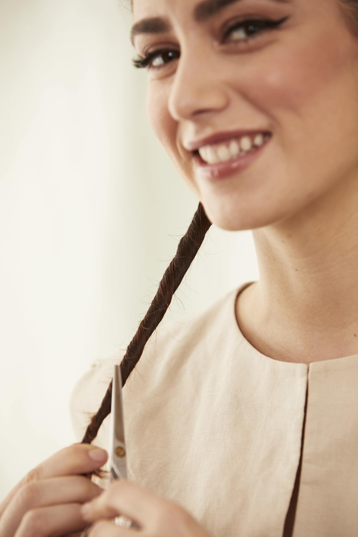Une femme s'éclaircit les cheveux avec des ciseaux à effiler