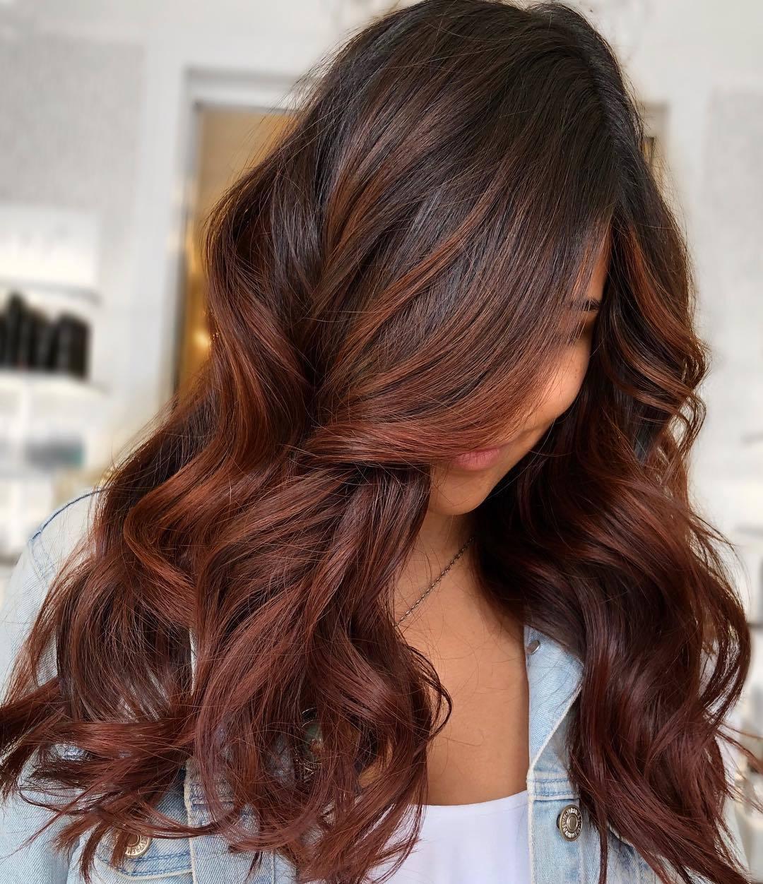 Femme aux cheveux bruns avec des mèches de cheveux roux et châtains