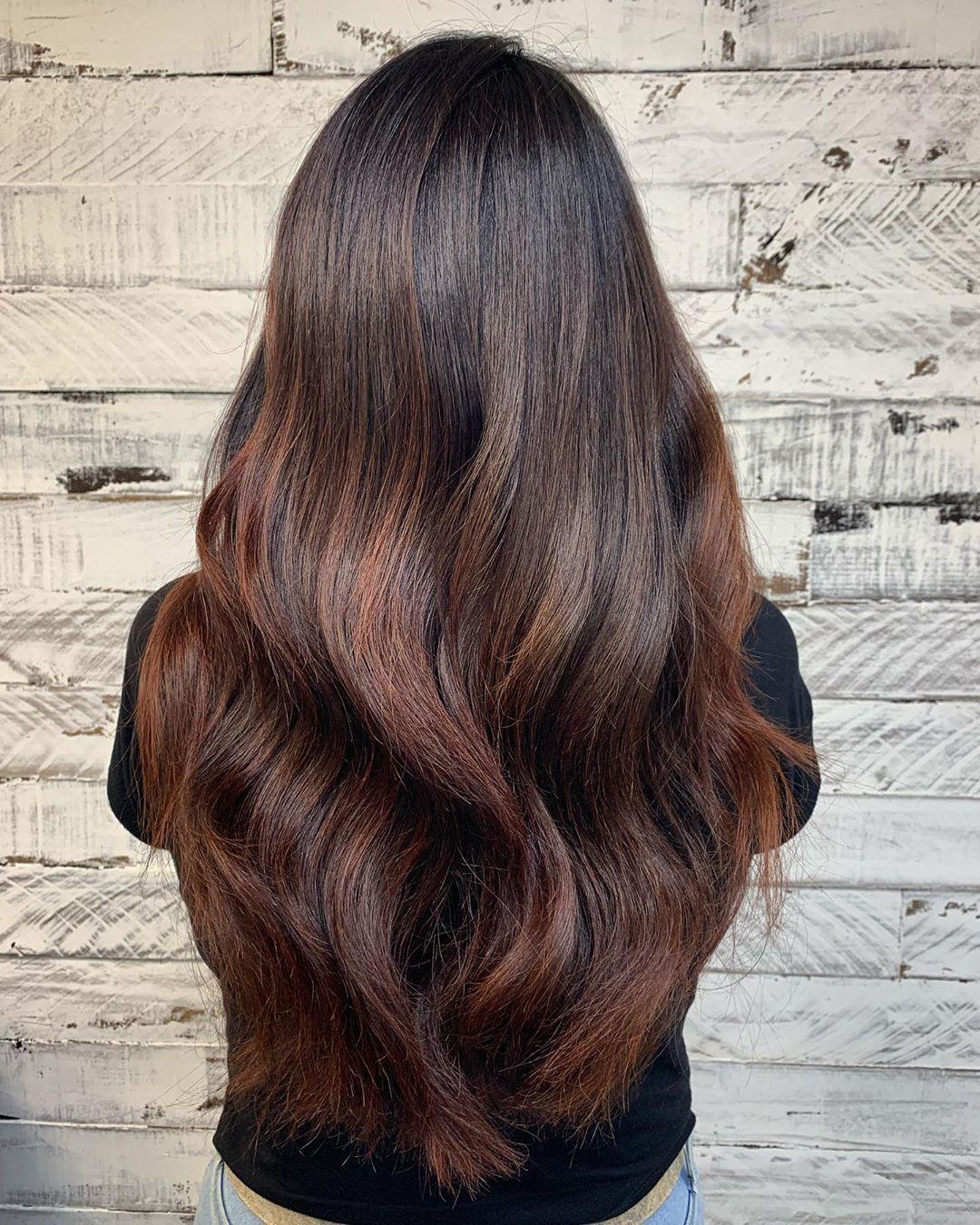 Femme aux longs cheveux châtains aux reflets subtils