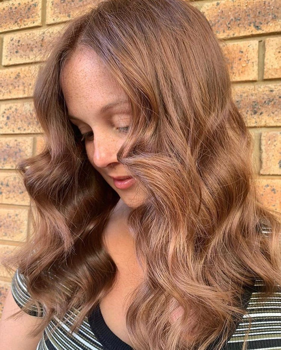 Femme aux cheveux caramel et châtain, coiffée en vagues